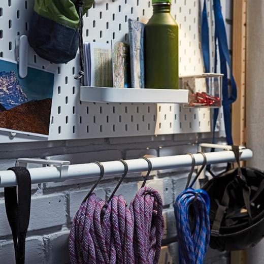 Ropes and climbing gear hanging from hooks placed on a white IKEA HUGAD curtain rod.