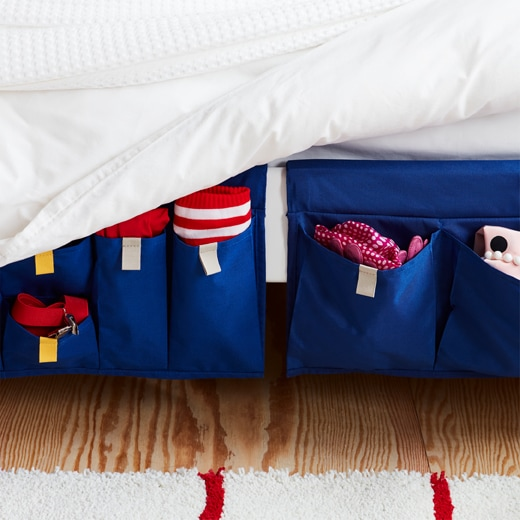 A blue MÖJLIGHET textile bed pocket for good-to-have storage hung on the side of a bed.