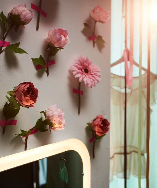 A wall covered with SMYCKA art flowers, attached one by one with pink tape.