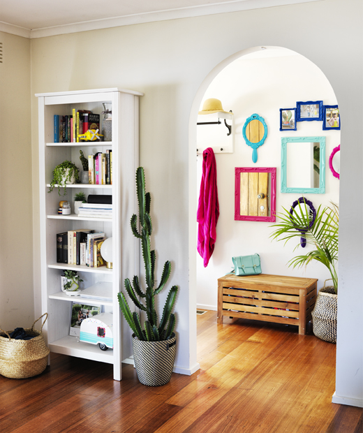A white bookcase and large cactus next to an archway leading through to a hallway with colourful mirrors on the wall.