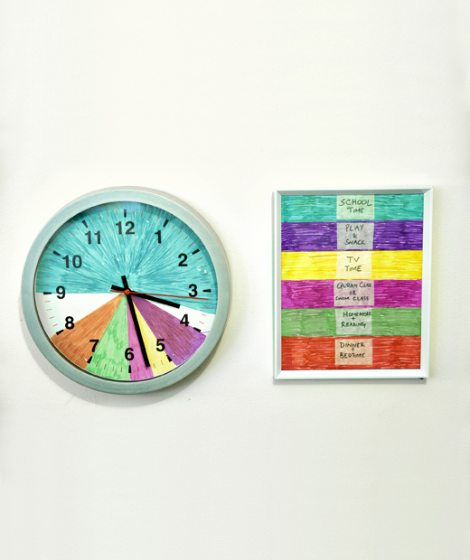 A wall clock divided into coloured segments next to a colour-coded key for family activities.
