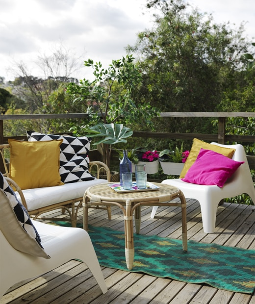 A deck area with rattan sofa and table, plastic armchairs, a colourful rug and cushions.