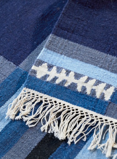 A close-up of a handmade striped TRANGET wool rug in white, black, grey and different blue colours.