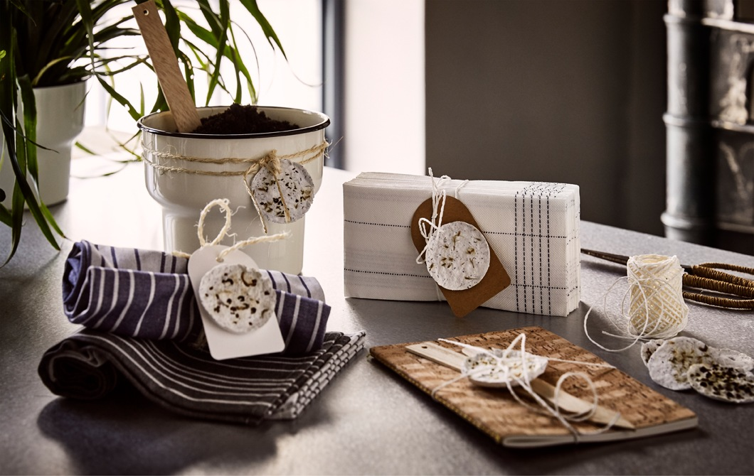 A beige plant pot, a brown notebook, textile napkins and paper napkins with home-made plant pods tied around them.
