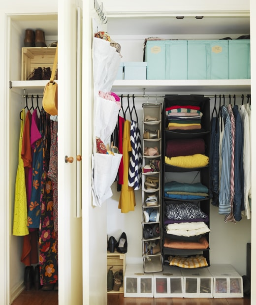 Two open in-built wardrobes with hanging storage and boxes filled with colourful clothes and shoes.