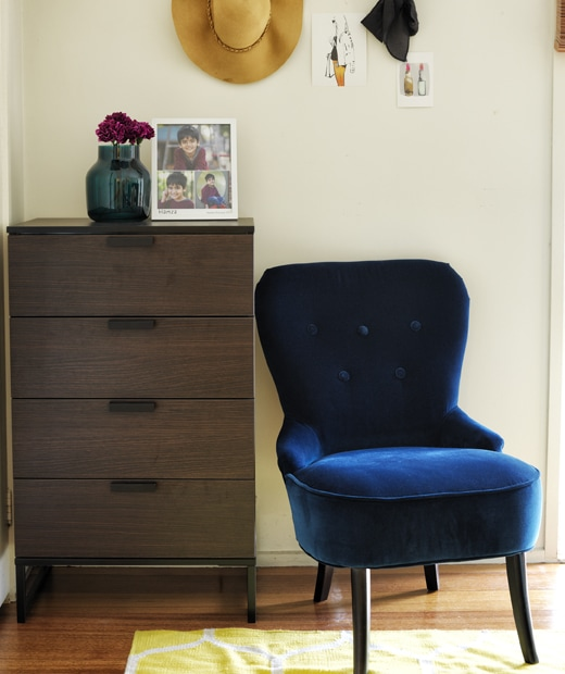 The corner of a white bedroom with a dark wood chest of drawers and dark blue velvet armchair.