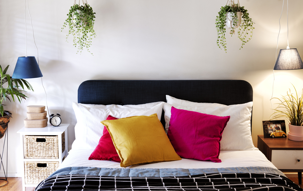 A double bed with colourful cushions and layered bedspreads, with two bedside tables, pendant lamps and hanging planters.