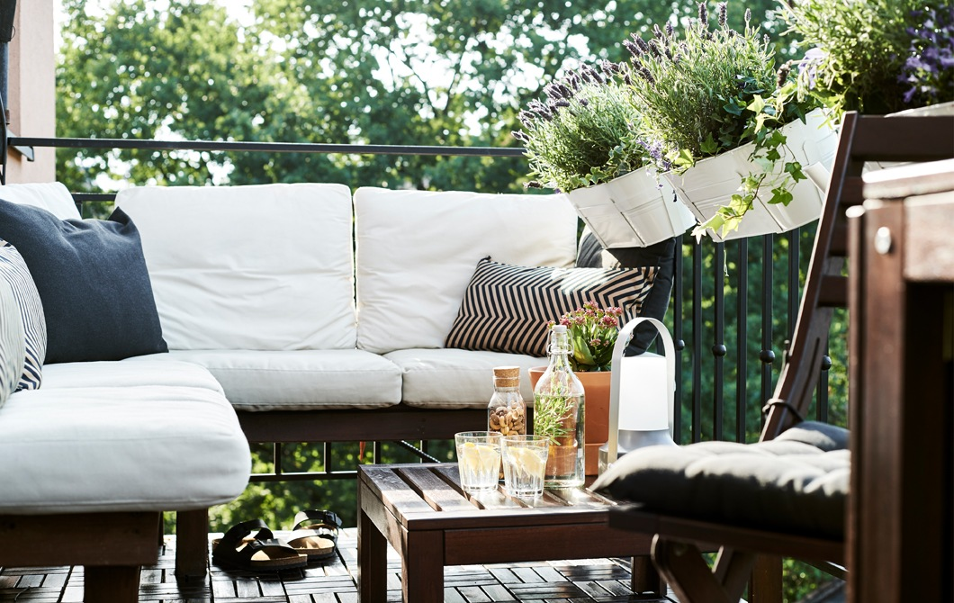 Dark wooden furniture with white cushions on a balcony with pot plants.