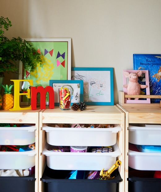 Toys stored in plastic trays in a wooden frame, with plants, pictures and books on top.