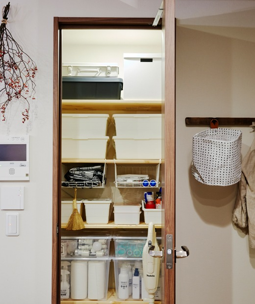 An open cupboard with white storage boxes stacked on shelves inside.