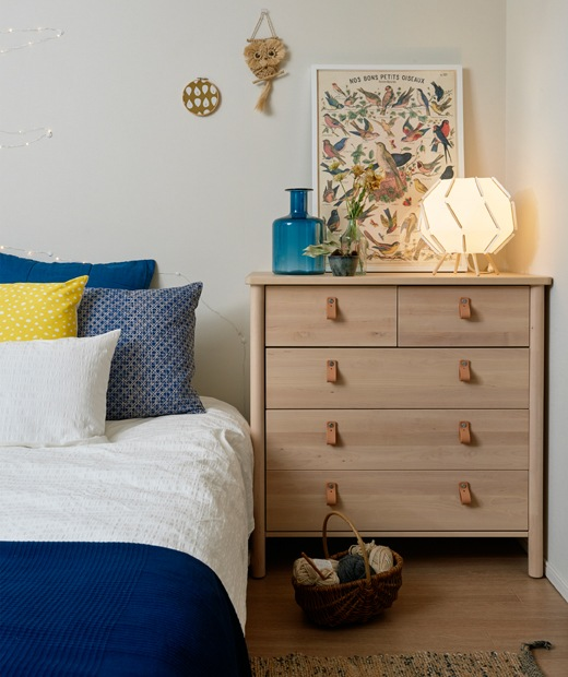 A bedroom with a pale wooden chest of drawers and bed dressed with blue and white bedding.