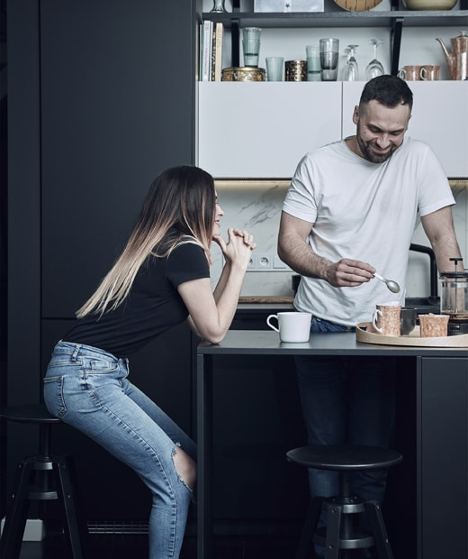 Katarzyna sitting on a bar stool at the black kitchen island where Mikolaj stands preparing coffee.