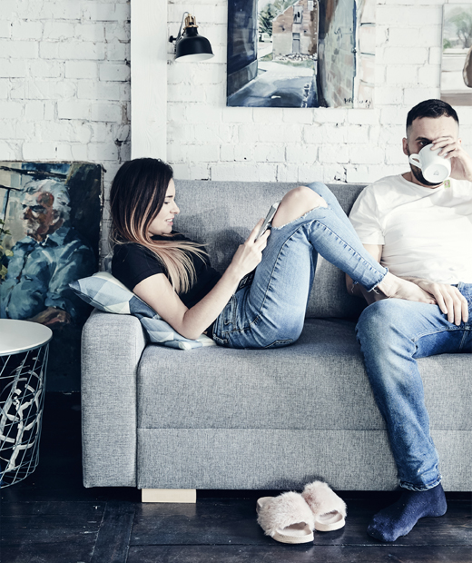 A portrait of Katarzyna and Mikolaj relaxing on their grey sofa against a white painted brick wall.