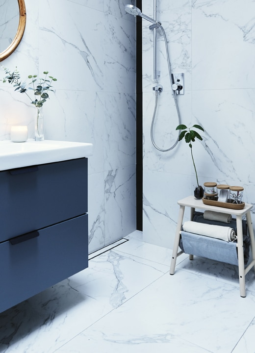 A grey washstand in a bathroom with white marble wall tiles, a wall-mounted shower and wooden stool with jars on top.