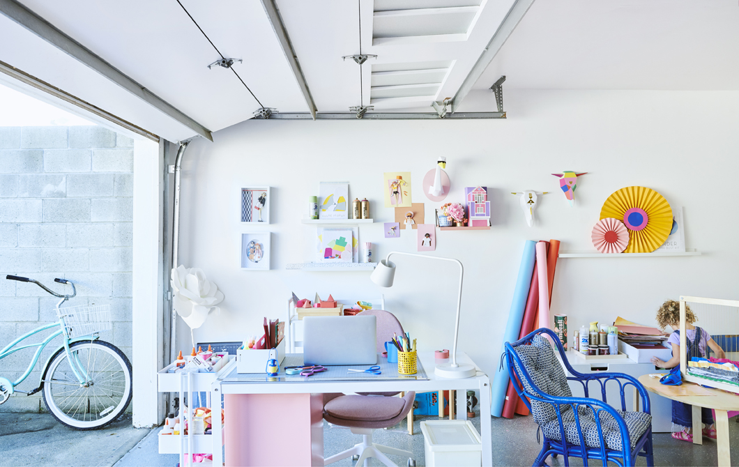 A colourful workspace with desk, trolley, chairs and wall displays, in a garage with the roller door open.