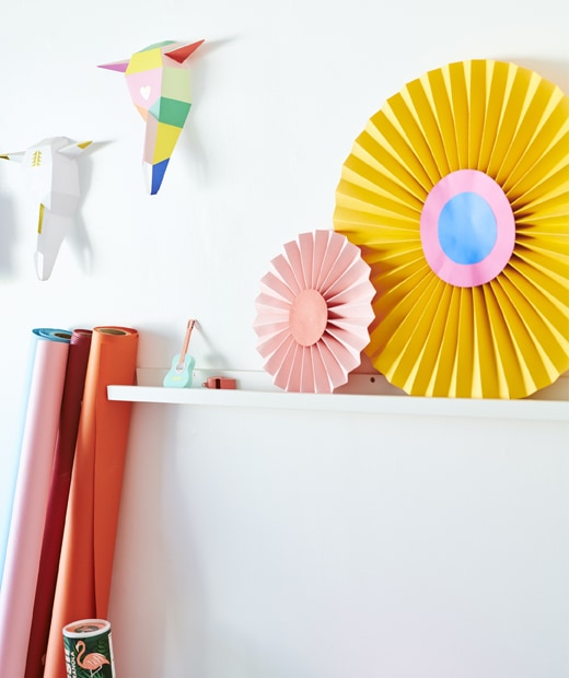 Colourful paper shapes displayed on a white picture ledge on a white wall.