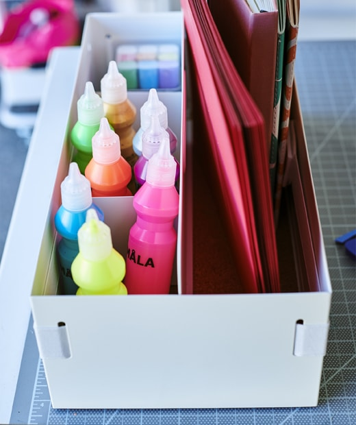 Tubes of colourful paint and notebooks stored in a white desk organiser.
