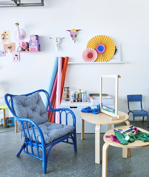 A weaving loom and fabric on two wooden side tables, a blue armchair, and colourful artwork on a white wall.