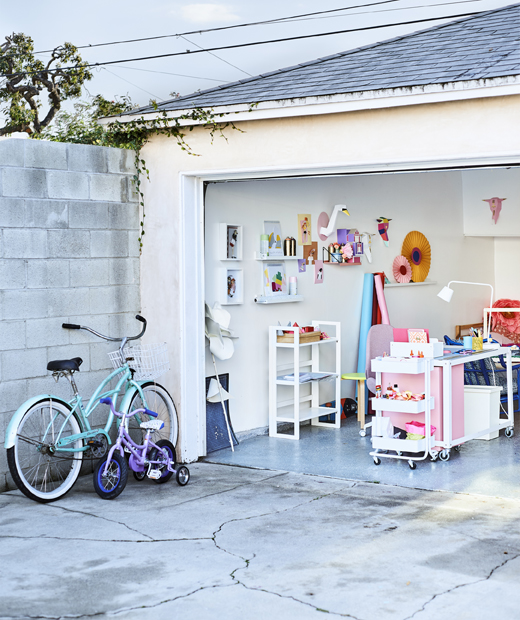 Looking into a colourful home office in a garage from the concrete driveway.
