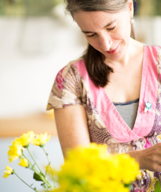 A close-up of Edna arranging yellow flowers.