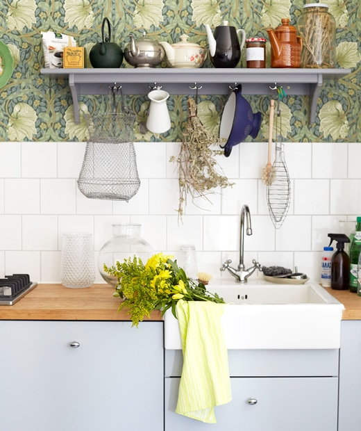 Pale grey kitchen cupboards, wooden worktops and a white sink, with tiles and a grey shelf above.