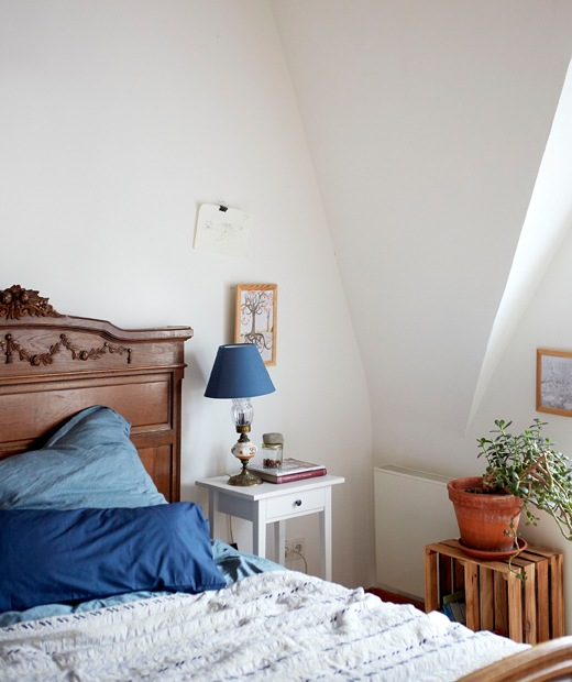 A white bedroom with pitched ceiling, dark wooden bed with blue bedding and white bedside table.