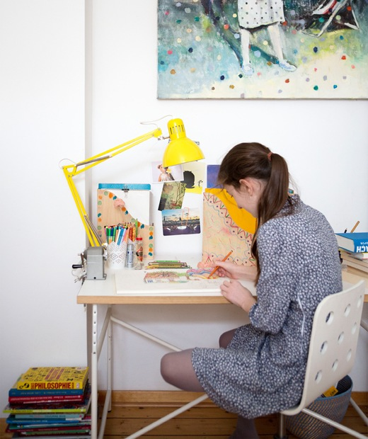 Karlotta drawing at her desk with yellow desk lamp and box files.