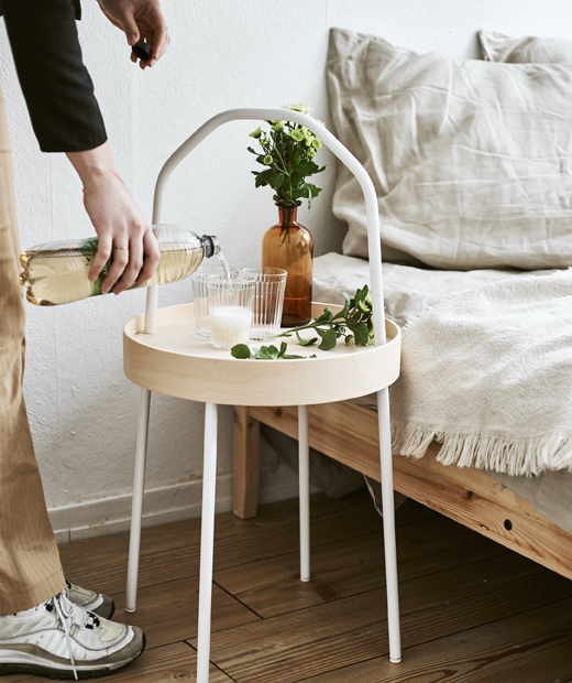 Yvet pours a drink into a glass on a light wood side table with white handle next to a bed.