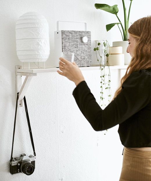 Yvet places a glass on a shelf with a lamp, speaker and plants.