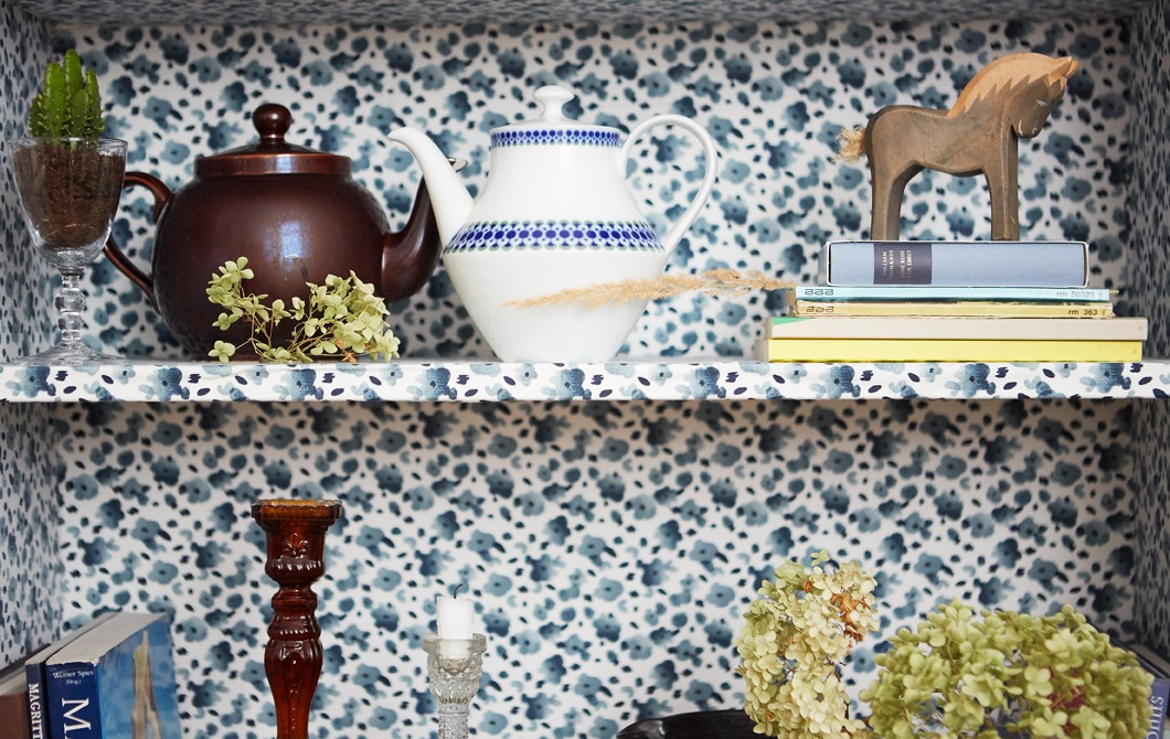 Teapots, books and ornaments on shelves with a blue floral pattern.