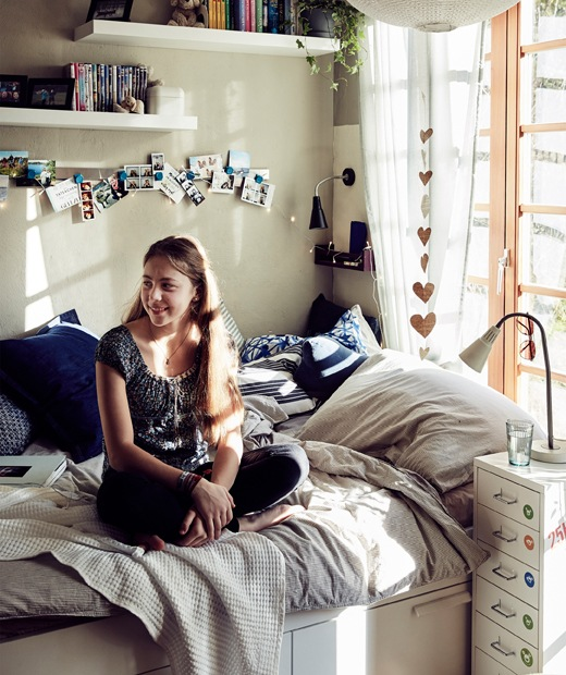 Malin sitting on her bed with neutral bedding, blue cushions and shelves on the wall above.