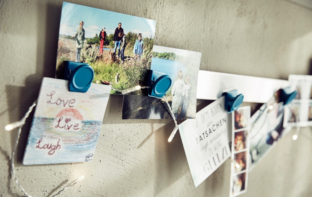 A close-up of photographs and pictures clipped on a rail.