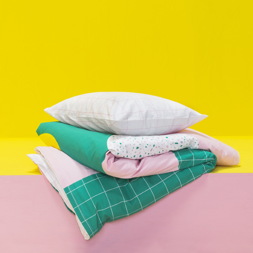 Pink and green patterned bedding folded up on a pink and yellow shelf.