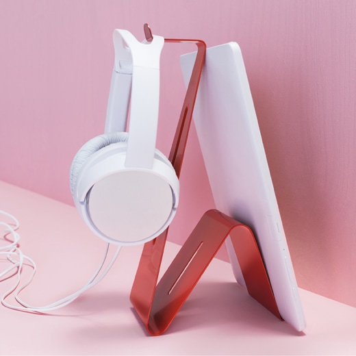 A white tablet and headphones on a red stand against a pink background.