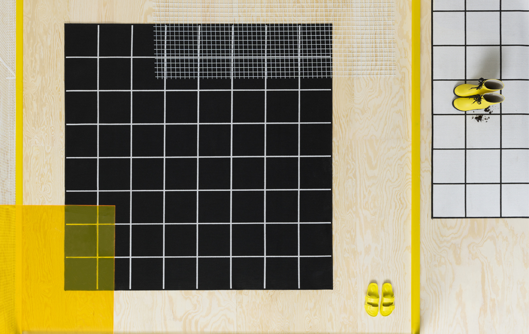 A black rug with white lines and a white rug with black lines on a light wood floor with yellow shoes.