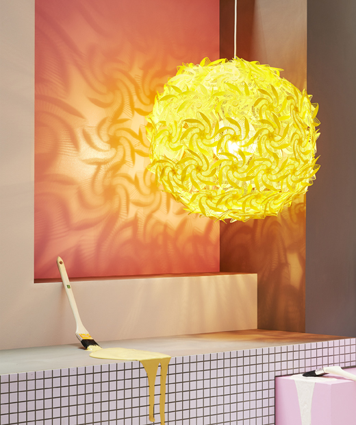 A large yellow pendant lamp with cut-out designs casting a decorative shadow against a red wall.