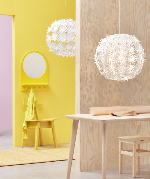 Two large white pendant lamps with floral design hanging in a pink, yellow and light wood room.