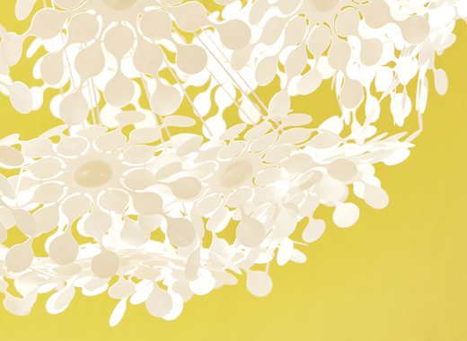 A close-up of a lamp with white cut-out flowers on a yellow background.