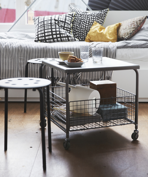 A table on wheels with storage basket underneath, two small stools and a daybed.