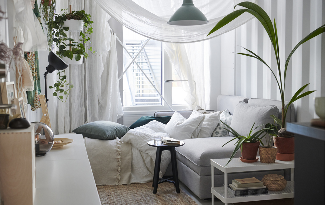 A white bedroom with neutral textiles, sheer curtains draped around the sofa bed and pot plants.