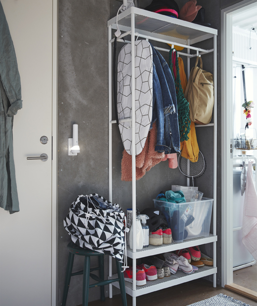 A tall open storage unit with shoes, coats and an ironing board on shelves and rails, next to a door.
