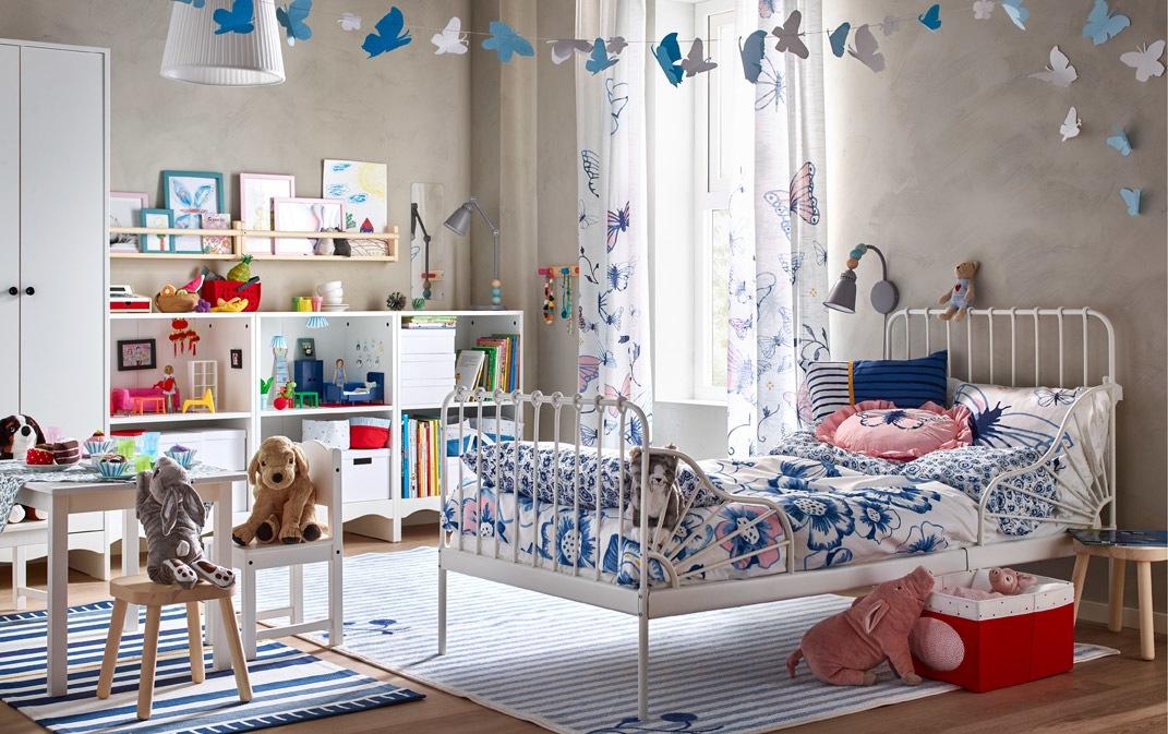 Hiasi kamar si kecil dengan seri tekstil tempat tidur SÅNGLÄRKA berwarna biru dan putih, termasuk seprai bercorak bunga-bunga dan gorden tipis bercorak kupu-kupu biru dan merah muda.