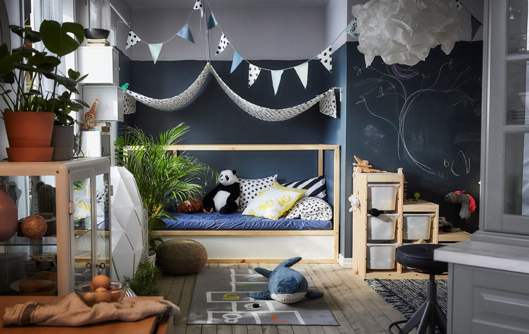 A play area with a fabric canopy over a day bed, soft toys, patterned rug and storage boxes.
