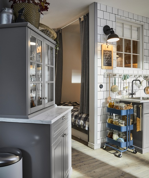 Grey kitchen cupboards, a blue trolley and hooks along a white tiled wall above a sink.