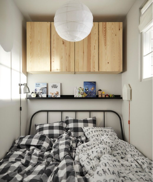 A bed with two duvets, books on a picture ledge above, and wooden cupbords on the wall.