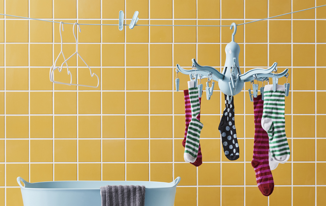 Socks on a blue hanging dryer, pegs and hangers on a clothes line against a wall of yellow tiles.