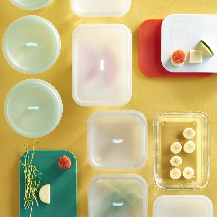 An overhead view of food storage boxes of different shapes and sizes with lids.