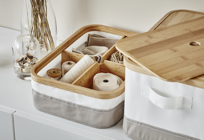 A close-up of white and grey storage boxes with wooden lids and sewing items stored in wooden compartments inside.