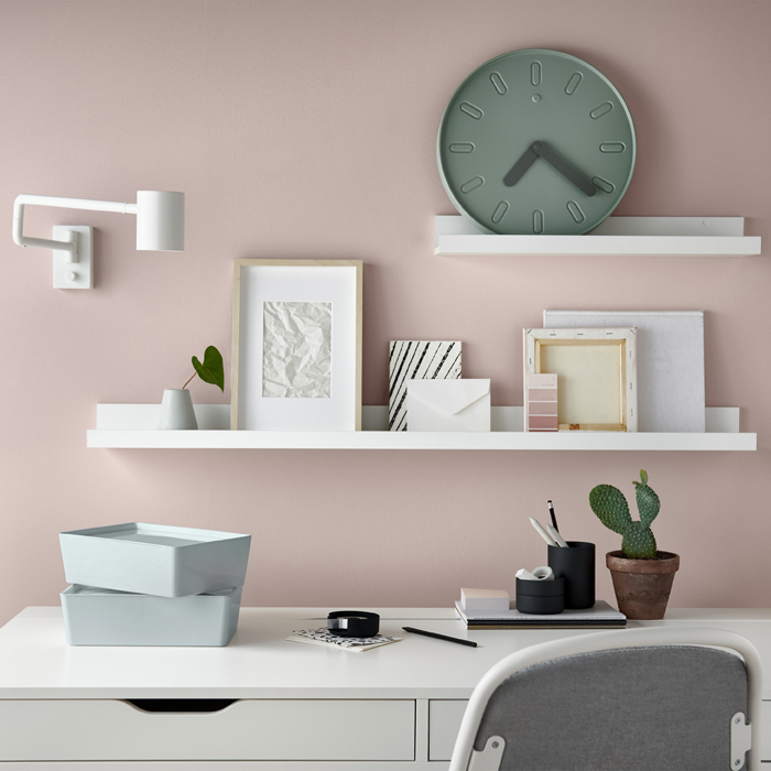 A white desk against a pink wall, with pictures and a clock displayed on white picture ledges.