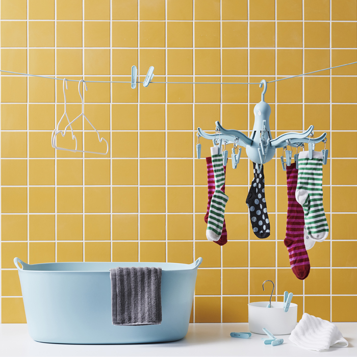 Socks on a blue hanging dryer, pegs and hangers on a clothes line above a blue laundry basket against a wall of yellow tiles.